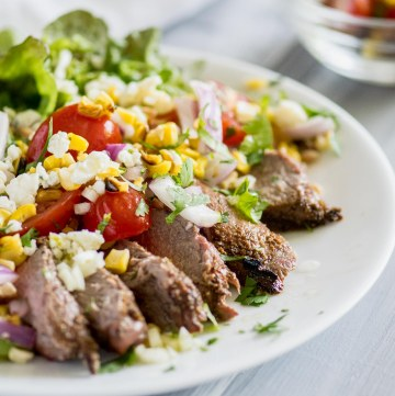 Salad with grilled steak, tomatoes, blue cheese and avocado on a white plate