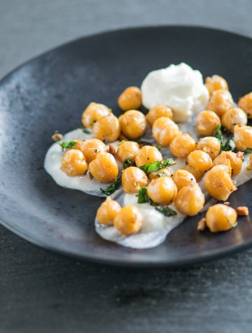 Pan roasted chickpeas on a yogurt base on a black salad plate