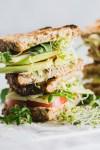 Stacked veggie sandwich with hummus, avocado, tomato & cheese