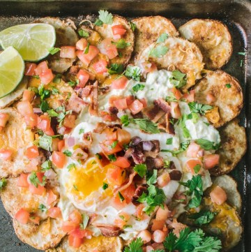 Nachos made with potato rounds topped with avocado crema and an egg
