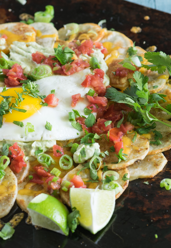 Close up of potato nachos topped with a fried egg and sliced green onions