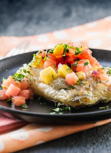 Grilled sea bass filet topped with watermelon mango salsa on a matte black plate