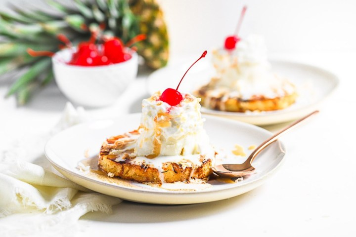Grilled pineapple slices topped with ice cream and bright red cherries