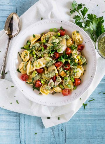 Overhead shot of tortellini pasta salad topped with bright red tomatoes and artichoke hearts
