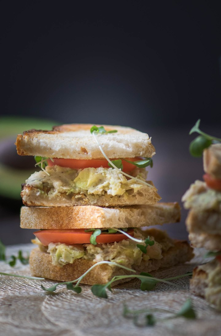 Double stacked Vegetarian sandwich with avocado and white bean on toasted sourdough bread
