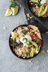 Overhead shot of a chicken burrito bowl topped with avocado slices and pico de gallo