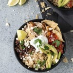 Overhead shot of a chicken burrito bowl topped with avocado slices and pico de gallo