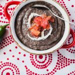 Creamy black bean soup with pico de gallo topping on a red and white napkin
