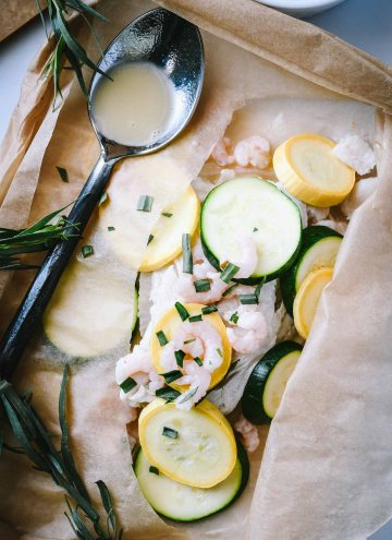 Dover sole filets in a parchment packet topped with yellow and green squash slices