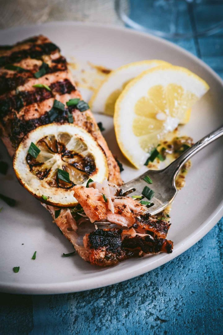 A bite of grilled salmon on a fork with the filet in the background