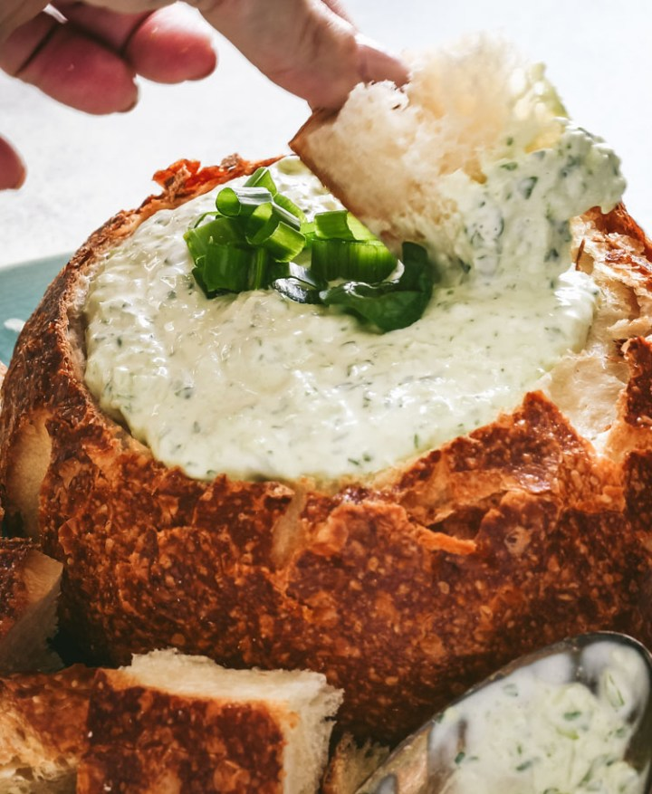 Close up of bread being dipped into spinach dip in a bread bowl