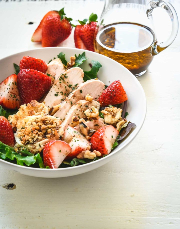 Salad topped with grilled chicken, strawberries and baked goat cheese rounds