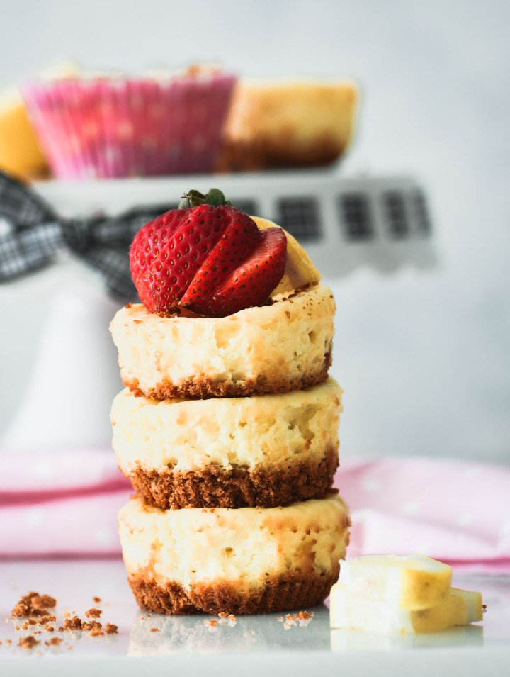 Three mini lemon cheesecakes stacked on top of each other then topped with a sliced strawberry