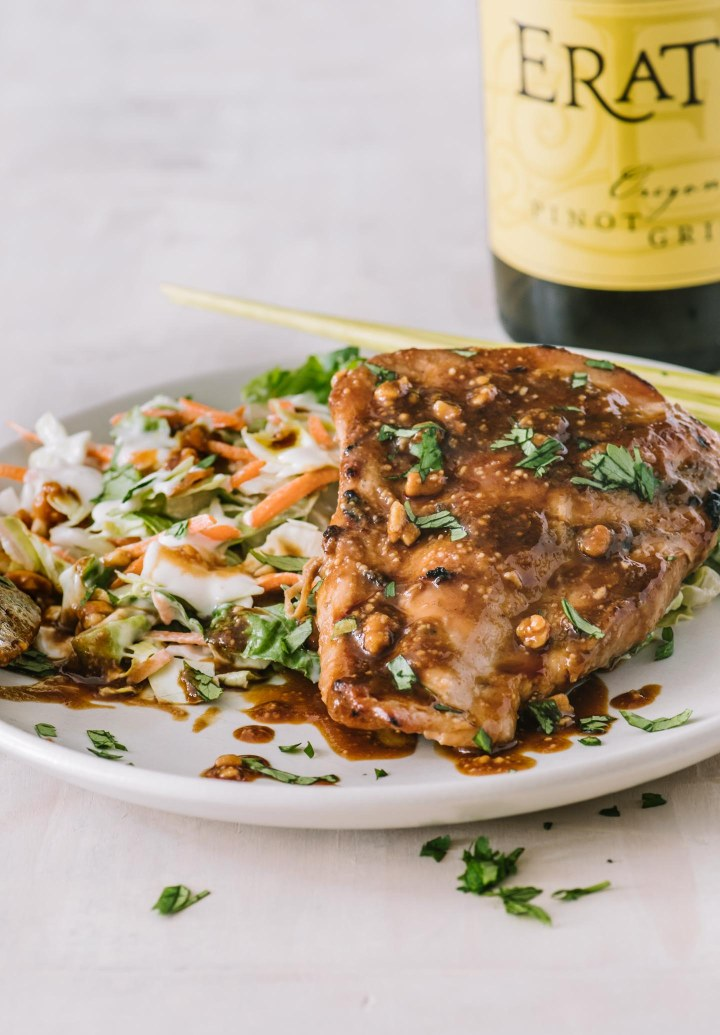 Chicken breast glazed with sticky Asian sauce with a bottle of Pinot Gris in the background