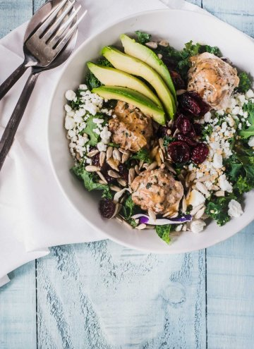 Kale salad greens topped with turkey meatballs, goat cheese and avocado