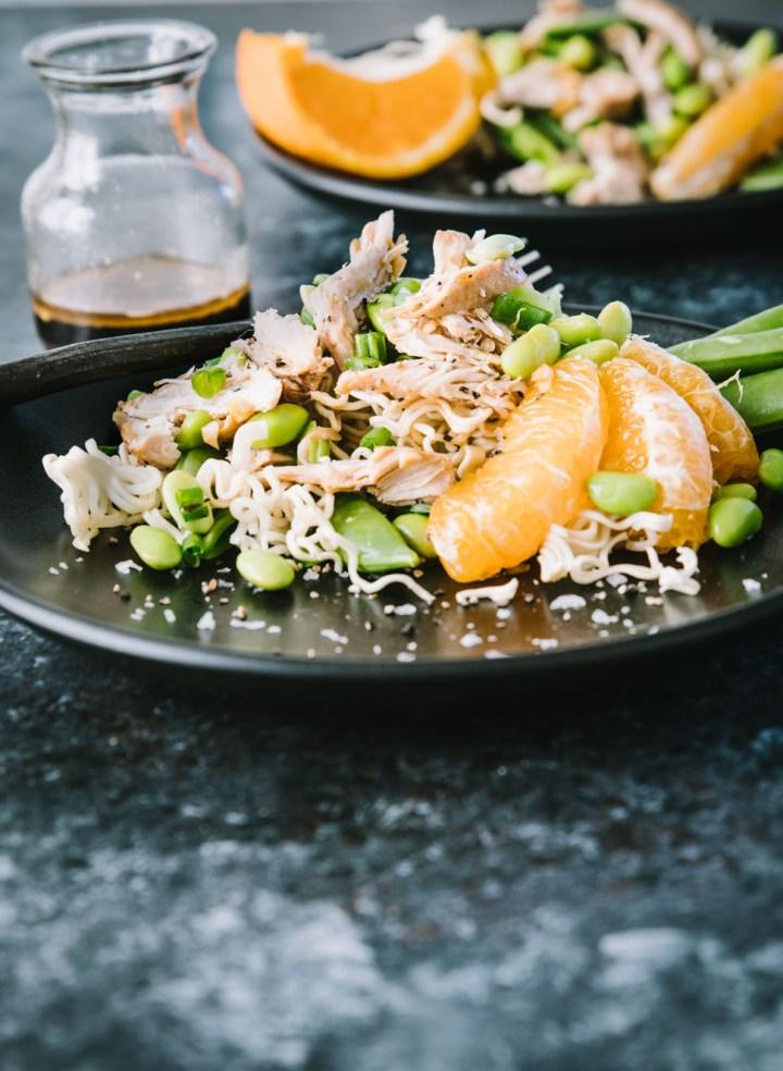 Asian Chicken salad with a ramen cake on a dark plate and dark background