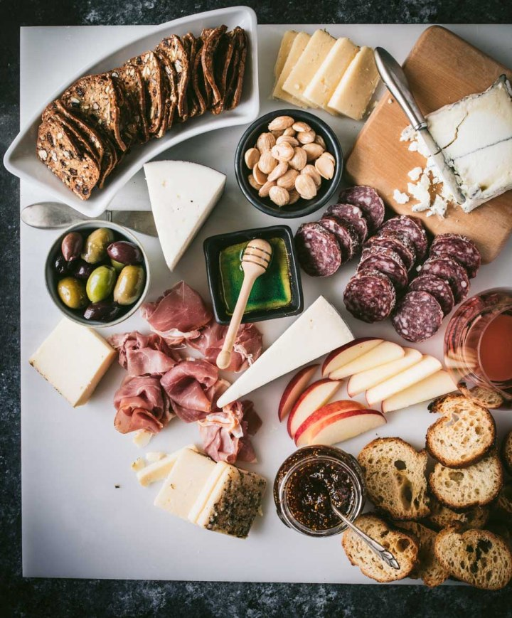 Cheeses, salami and crackers on a white marble board