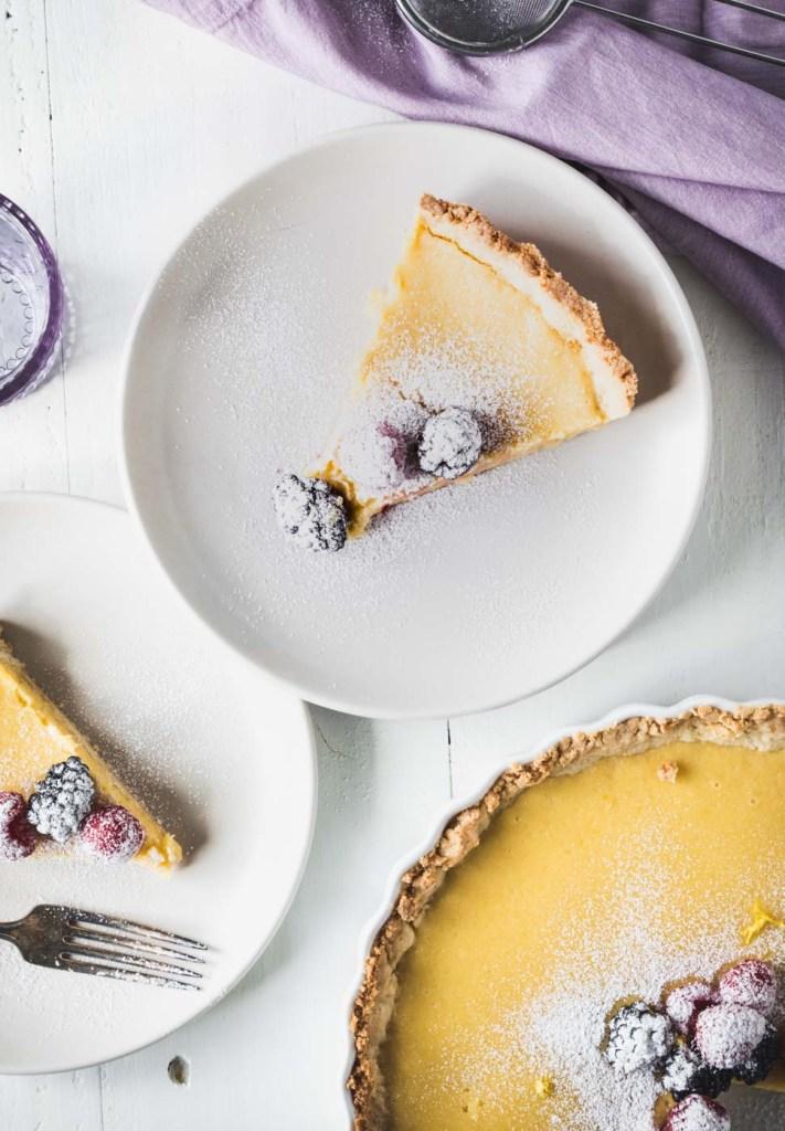 Two slices of lemon tart on white plates