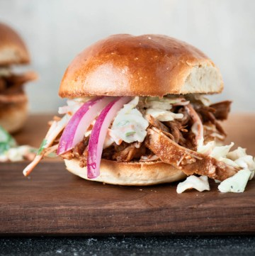 Close up of pulled pork slider topped with pickled red onions