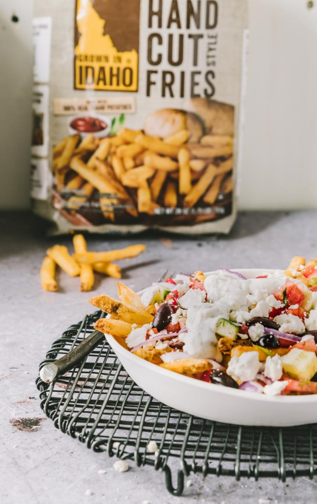 Oven baked fries topped with marinated tomatoes, peppers, feta and tzatziki sauce