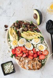 Cobb salad topped with grilled chicken, bacon, avocado, hard boiled eggs and strawberries.