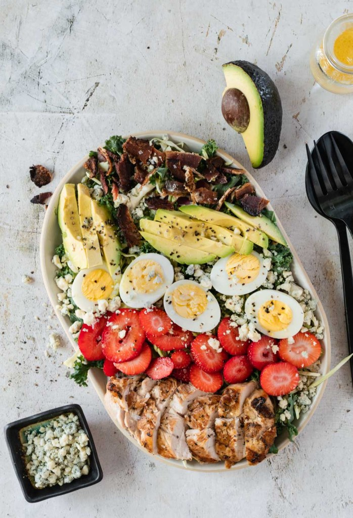 Cobb salad topped with grilled chicken, avocado, bacon and strawberries