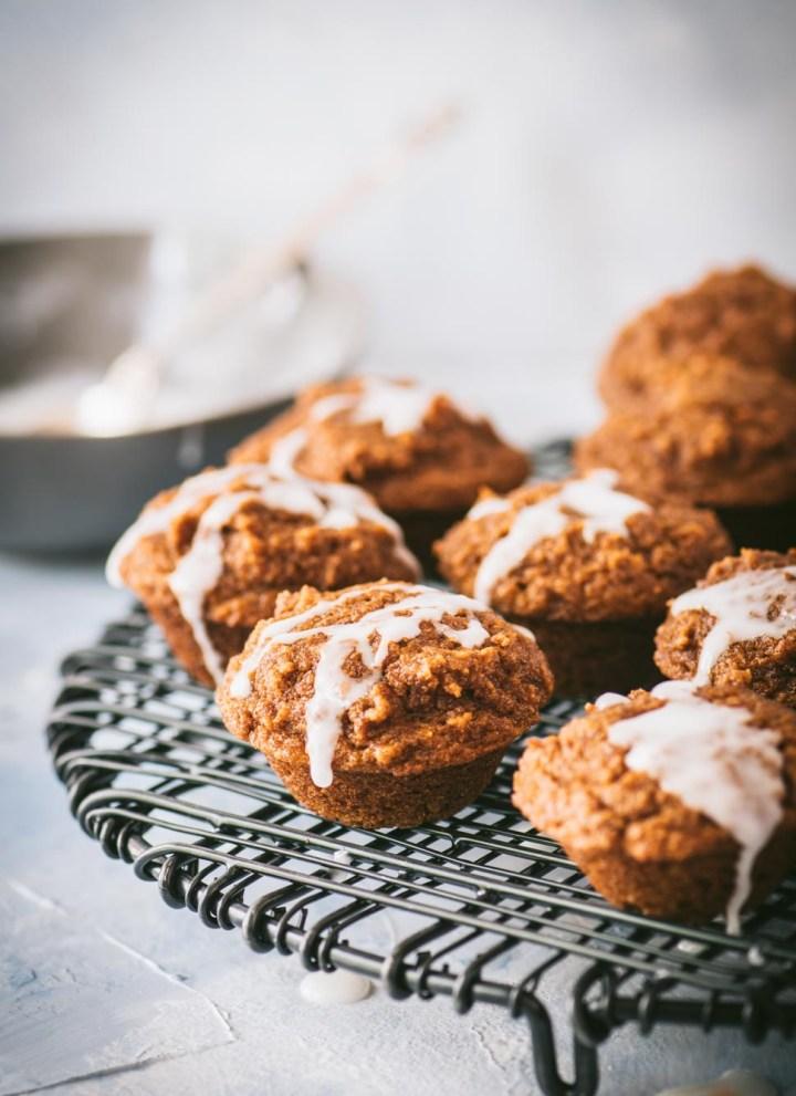 Close up of mini pumpkin muffins on a black wire rack