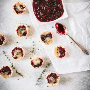 Cranberry brie tarts with a dish of cranberry sauce shot from overhead