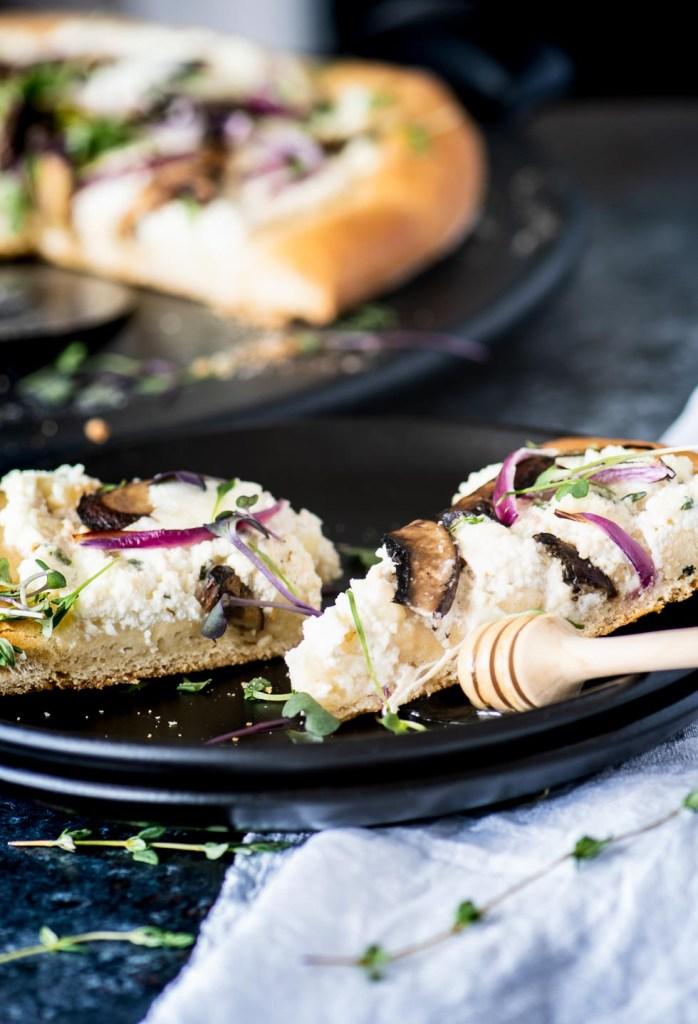Slices of ricotta mushroom pizza on matte black plates