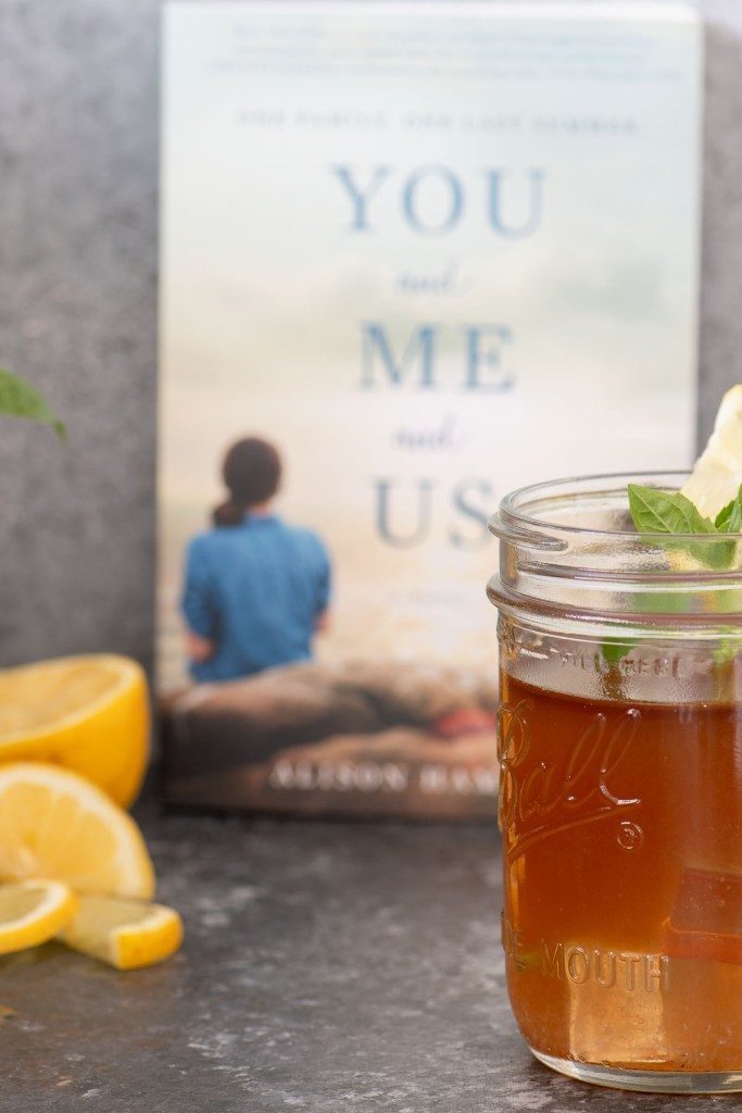 Bourbon Arnold Palmer with basil leaf garnish in front of book