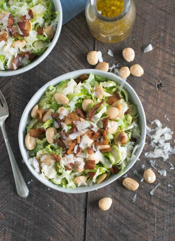Two bowls of shaved brussels sprouts topped with pancetta, marcona almonds and parmesan