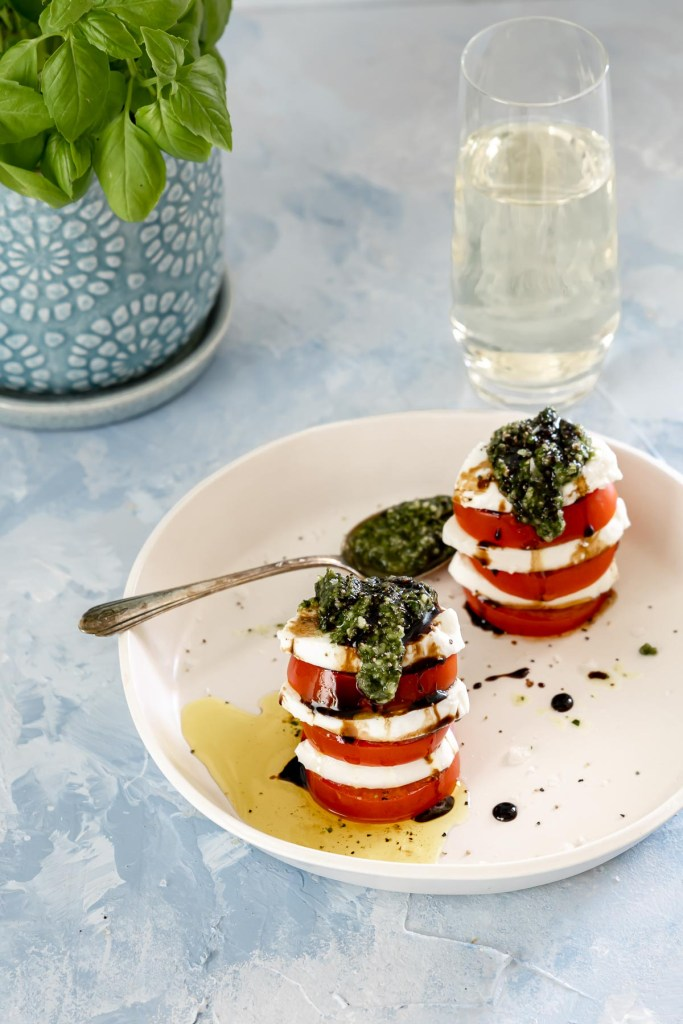 Two stacks of tomato, fresh mozzarella and basil pesto drizzled with olive oil and balsamic glaze