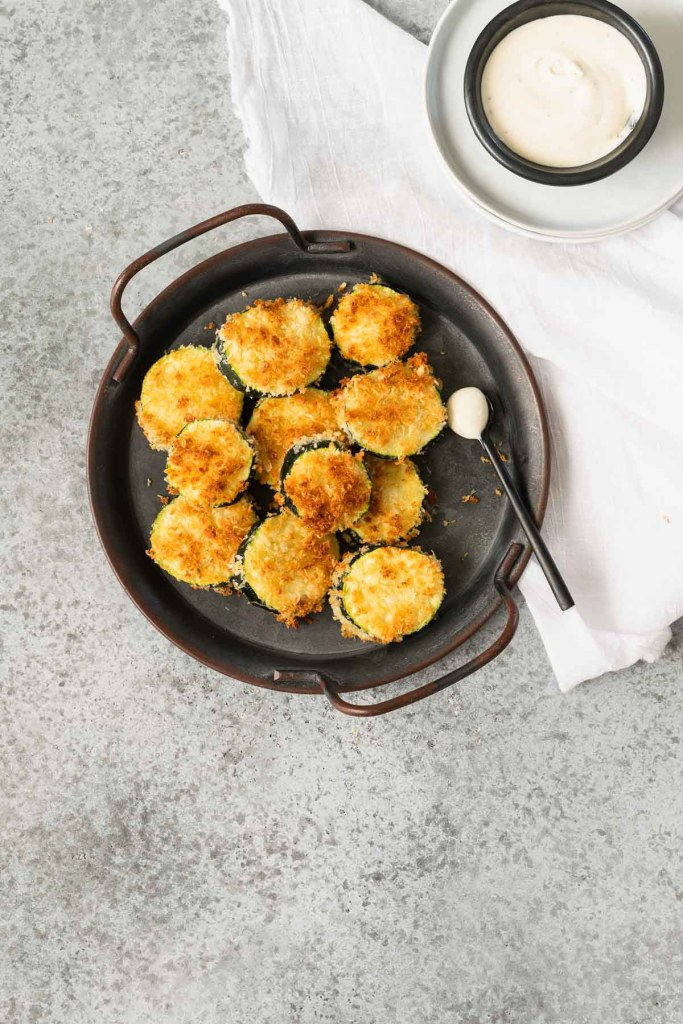 Air fried zucchini chips on a small metal platter with handles