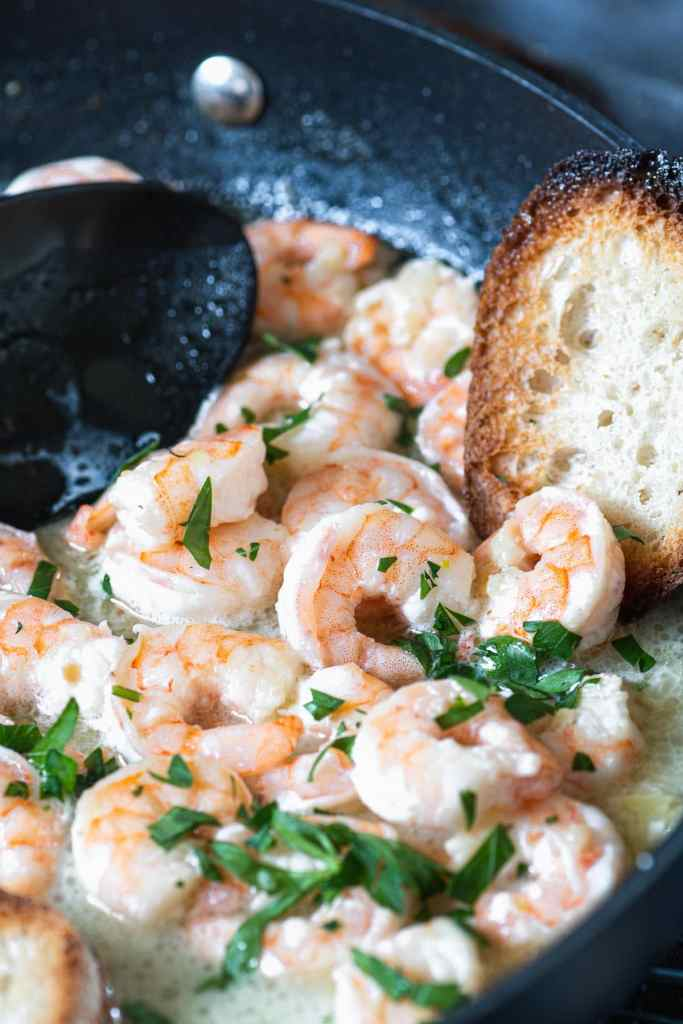 Close up of garlic shrimp in lemon butter with a slice of toasted bread on the side