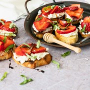 Crostini topped with sliced strawberries, goat cheese, basil and balsamic glaze