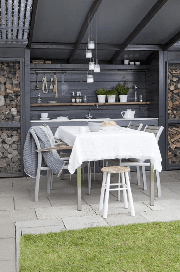 bungalow-style outdoor kitchen with log storage