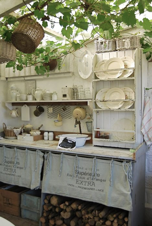White rustic, shabby chic outdoor kitchen with vintage dishware and cookware.