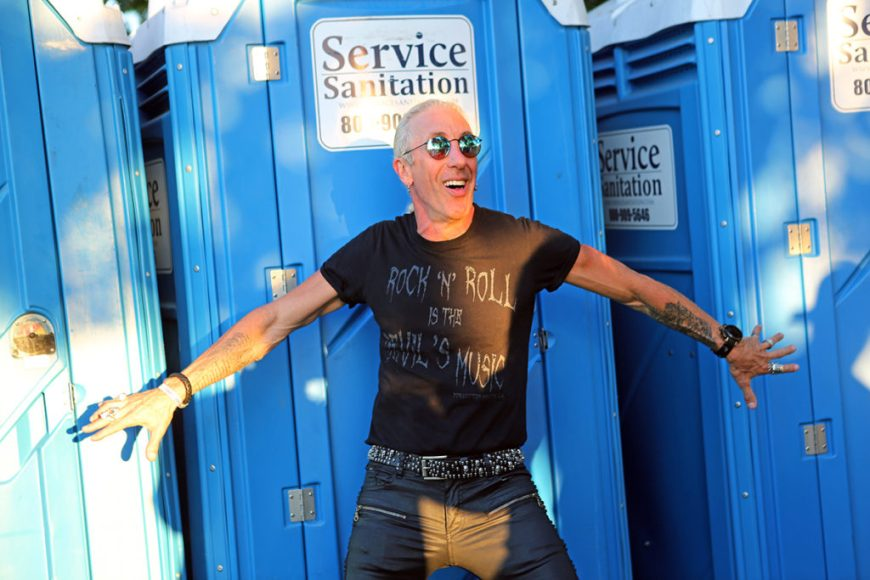 Picture of Dee Snyder posing with porta potties at Riot Fest 2016