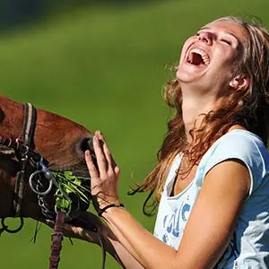 Photo d'une femme qui rit avec un cheval