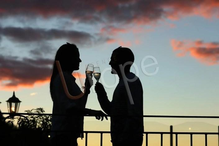 Image à contre-jour d'un couple avec une couple de champagne dans un hôtel
