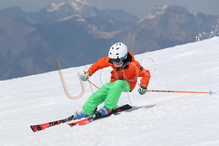 Jeune garçon qui descend les pentes de Chamrousse à ski avec la Chartreuse en arrière plan