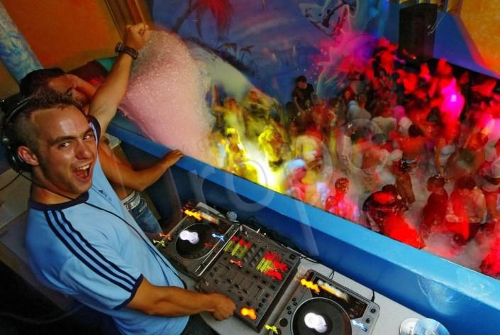 Photographie originale de mousse party en Corse avec un DJ devant les convives pour une agence d'événementiel