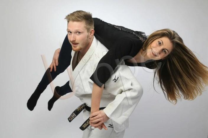 Prise de vue d'un homme sportif judoka porte sa femme sur le dos