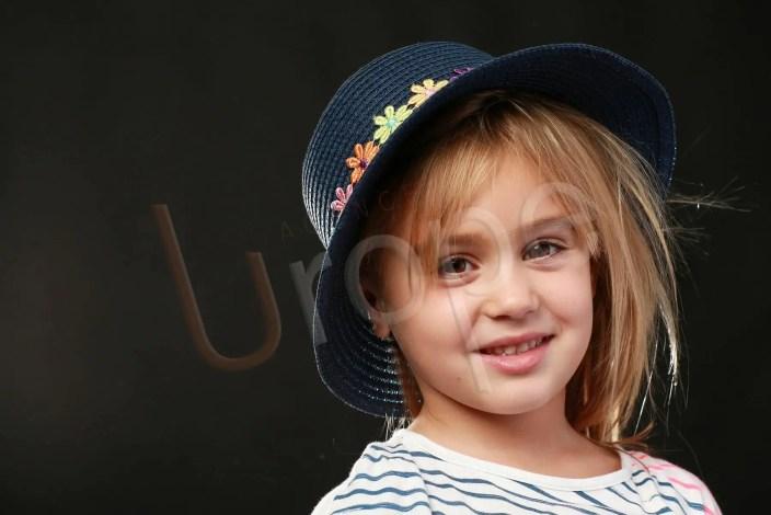 Portrait d'une jeune fille plein de gentillesse en couleur avec un chapeau sur fond noir sur Grenoble