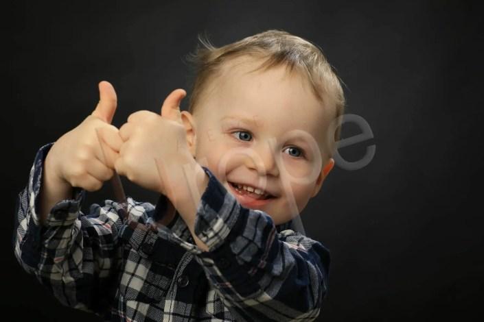 Photo d'un petit garçon qui tend ses pouces vers l'appareil photo