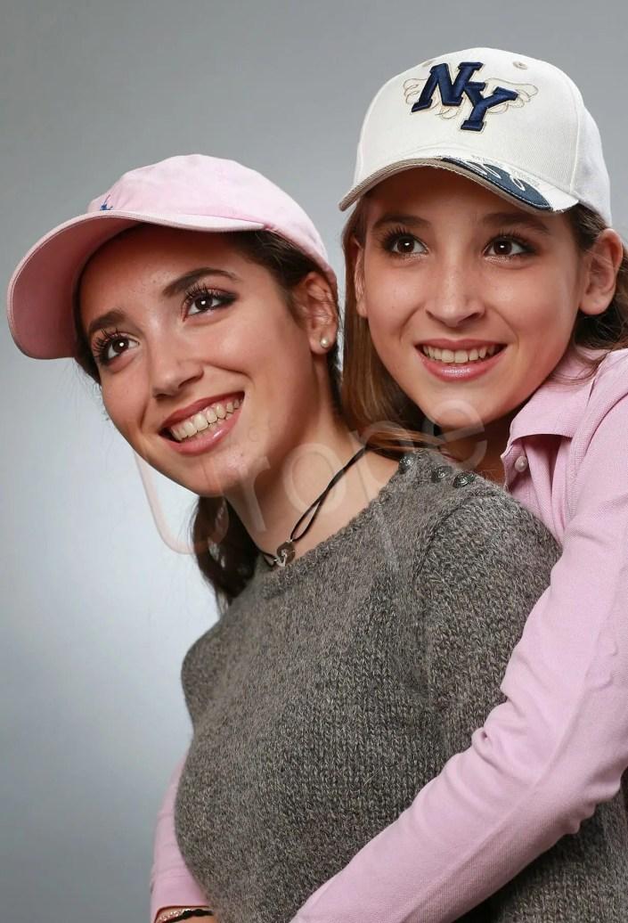 Photo studio de 2 soeurs qui portent une casquette avec des sourires