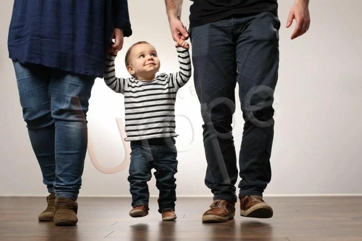 Image décontractée d'un enfant souriant qui tient la main de ses parents en marchant