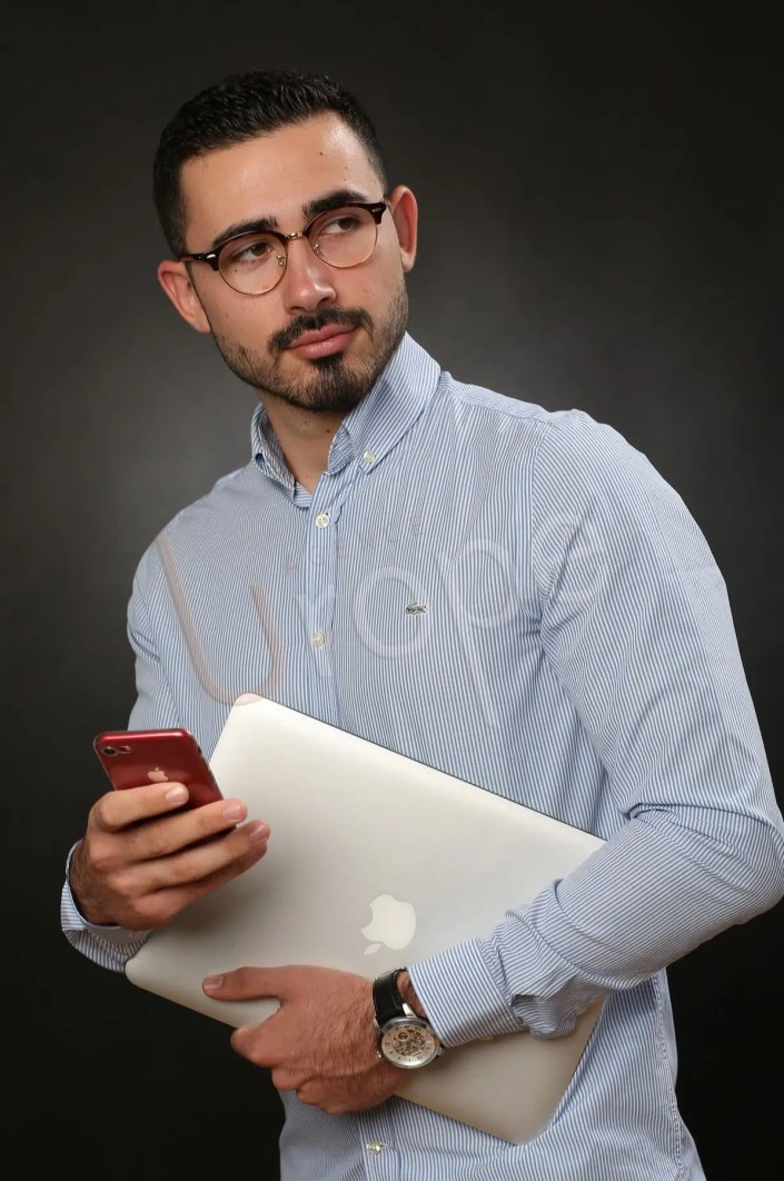 Portrait en studio pour les réseaux sociaux d'un jeune homme avec un ordinateur et un téléphone