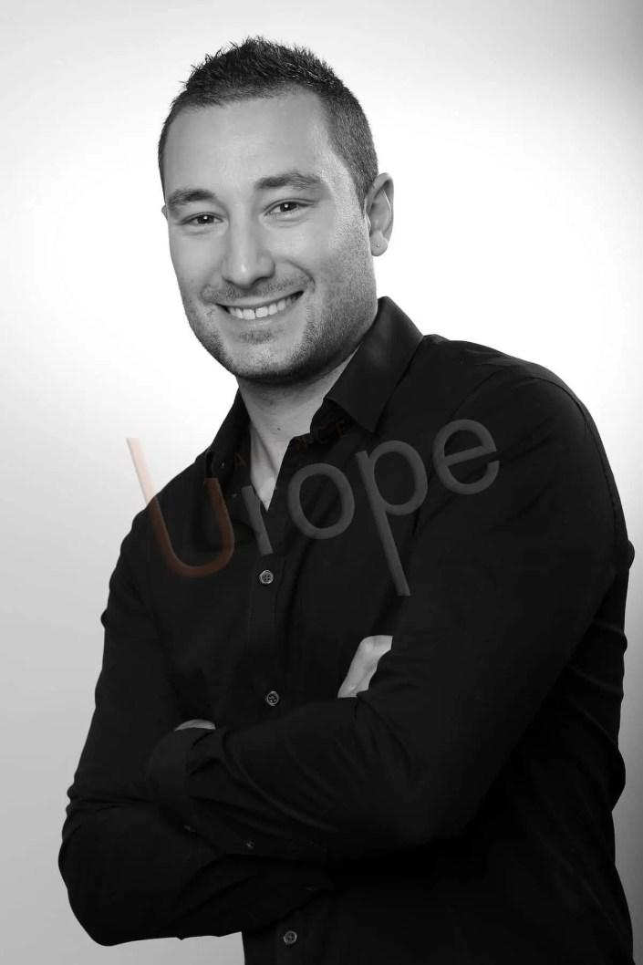 Image en noir et blanc réalisée par l'Agence Urope pour le CV d'un jeune homme avec arrière-plan gris