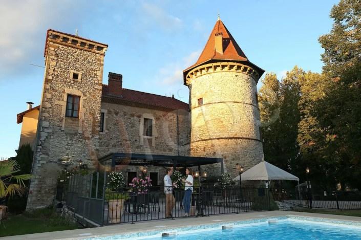 Image d'un couple en terrasse d'un château devant une piscine